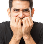 Closeup of nervous young man biting finger nails against white background